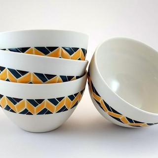 Bol en porcelaine, intérieur transparent brillant. Décor en bracelet avec motif ethnique de couleur noir, bleu et jaune moutarde.