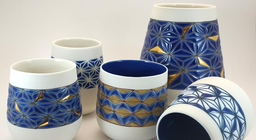 Ensemble de tasses et vase en porcelaine tournée, intérieurs émaillés en bleu cobalt ou transparent, différentes variantes du décor asanoha.