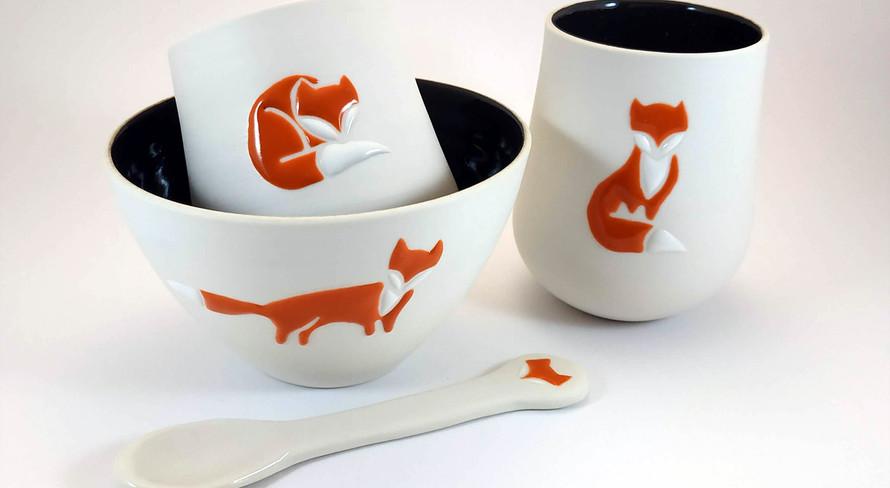 Ensemble de bols, tasse et petite cuillère en porcelaine, émail intérieur noir brillant et motif de renard stylisé dans plusieurs positions.
