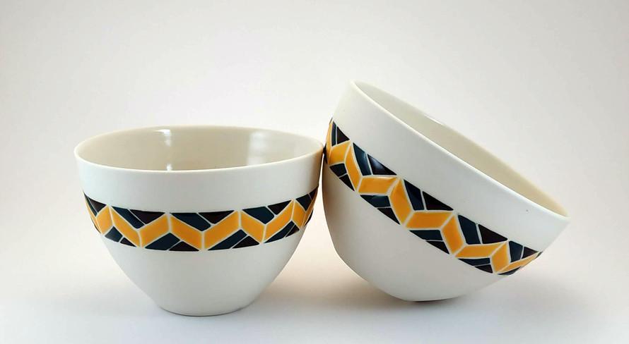 Deux bols en porcelaine avec un décor en émail brillant. Bracelet ethnique de couleur noir, bleu et jaune moutarde.