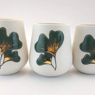 Tasse en porcelaine intérieur transparent brillant, décor extérieur relief brillant motif feuille de ginkgo vert foncé et base or.