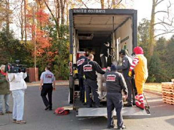 Charlotte, N.C., firefighters, Ronald McDonald and GSF-Lexington associates load a GSF truck with supplies to help NYC residents reover from the recent hurricane.