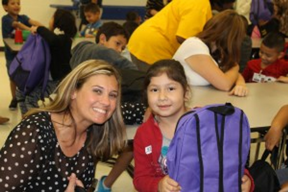 Joni Smith, Conyers GSF Foundation Chair, wears a matching smile with a first grader at the Conyers Backpack to School event.