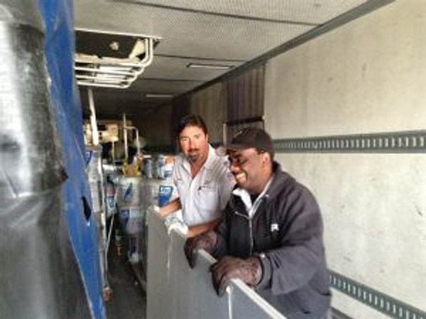 (l to r) Jeff Washington and Brian Littell (both drivers) help to unload the truck.