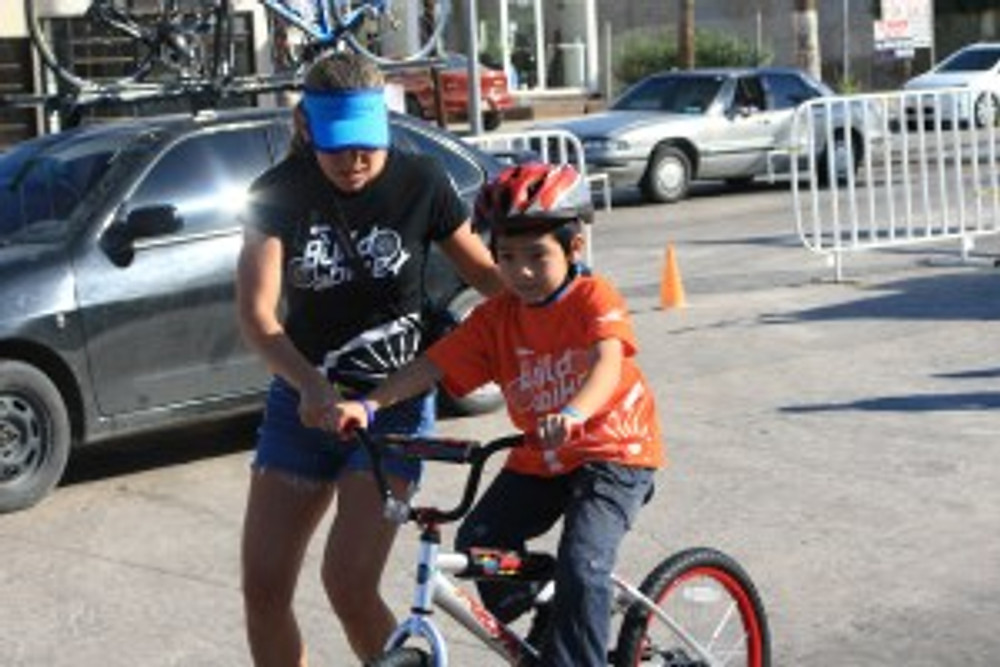 A volunteer helps this little boy ride a bike for the first time.