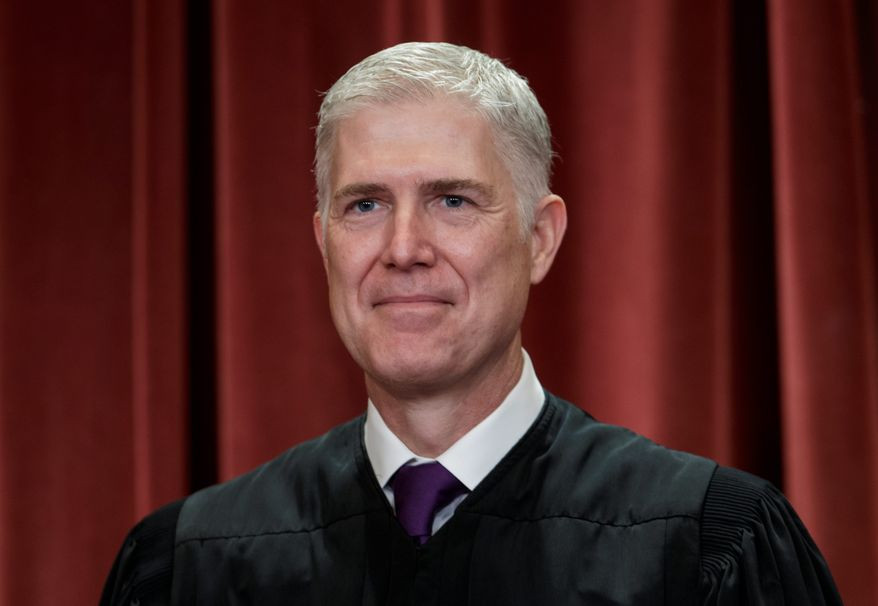 Associate Justice Neil Gorsuch, appointed by President Donald Trump, sits with fellow Supreme Court justices for a group portrait at the Supreme Court Building in Washington, Friday, Nov. 30, 2018.