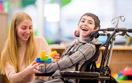 a smiling kid in a wheel chair with his caregiver