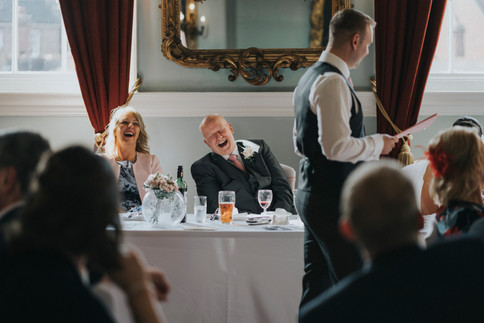 father and mother of bride laugh at speeches