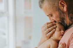 Dad kisses newborn daughter