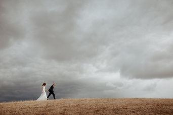 Bride & Groom Walking Up A Hill.jpg