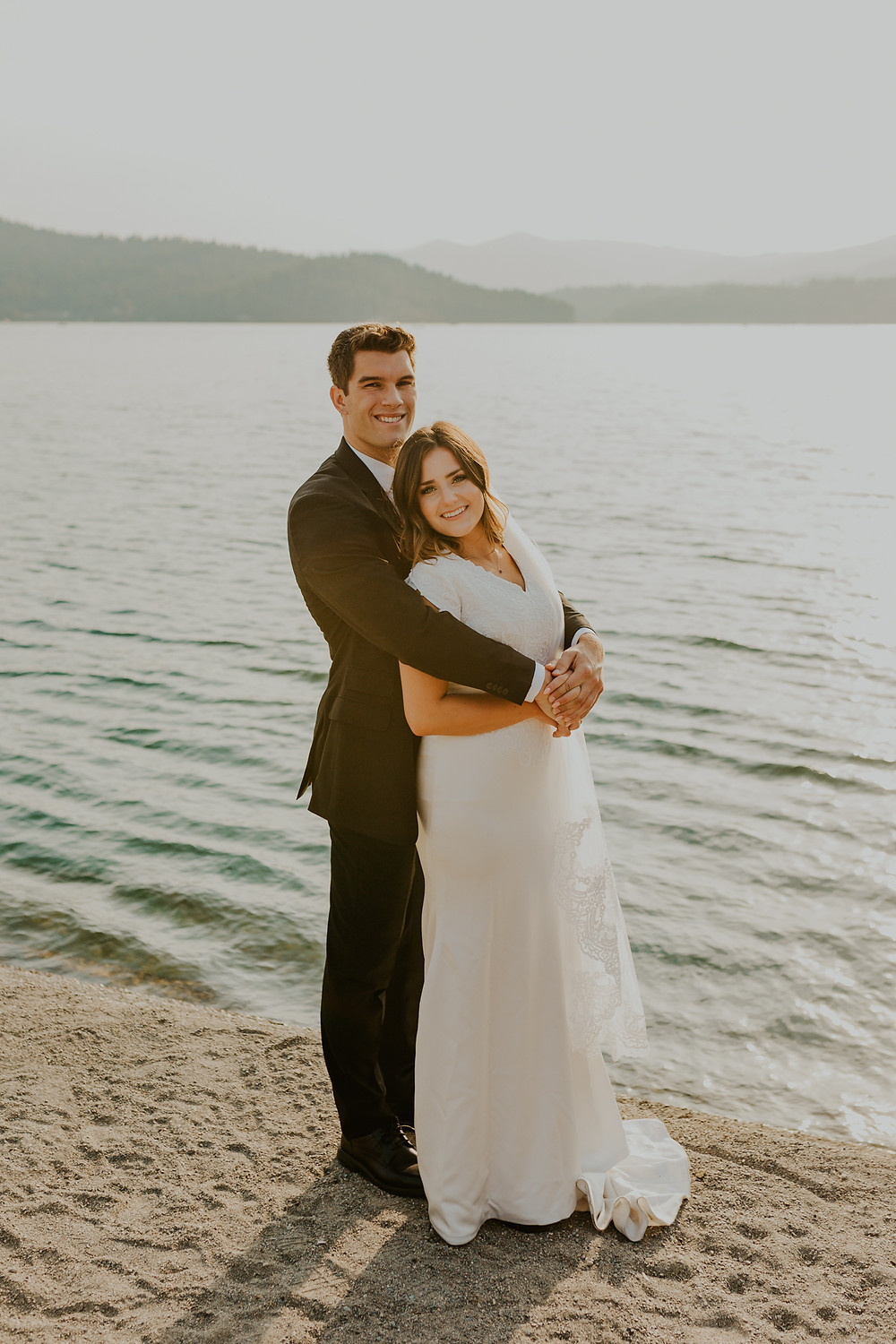 dreamy sunset lake bridals on lake coeurdalene north idaho, bride and groom adventure bridals on the water golden hour sunset dock and wake surfing photos, bridals on a boat