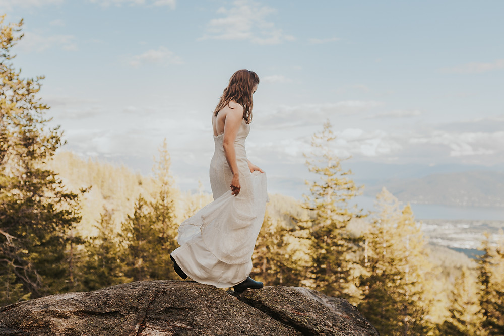 hiking bride bridals in the mountains overlooking the lake