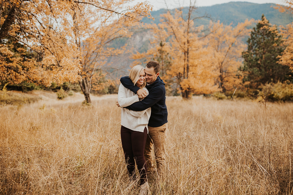 engagement session in north idaho with mountains, fields, and lake