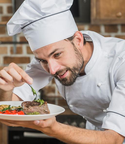 happy-male-chef-preparing-beef-steak-wit