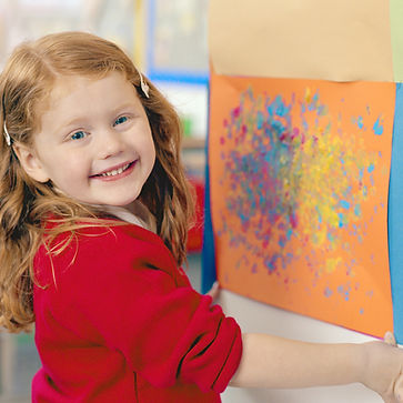 Young girl smiling with artwork