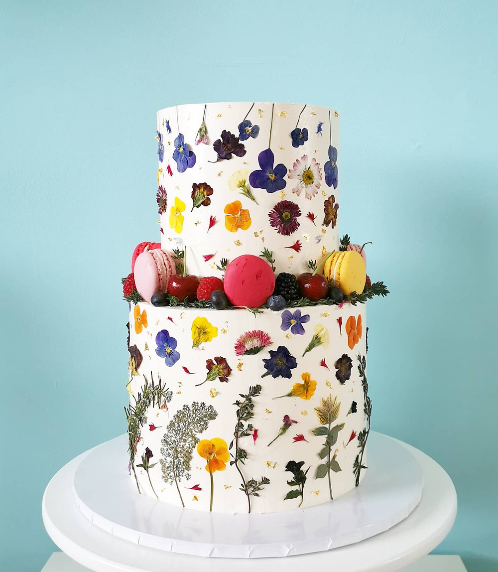 Tiered buttercream cake with edible flowers including pansy and macaroon details by the Macaroom