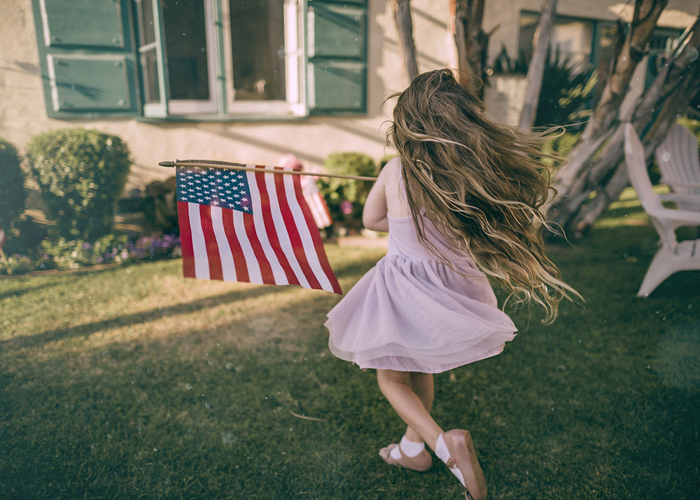 little girl waving American flag