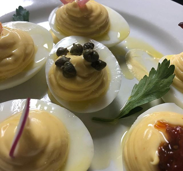 Deviled eggs._Pickled red onion. _Capers