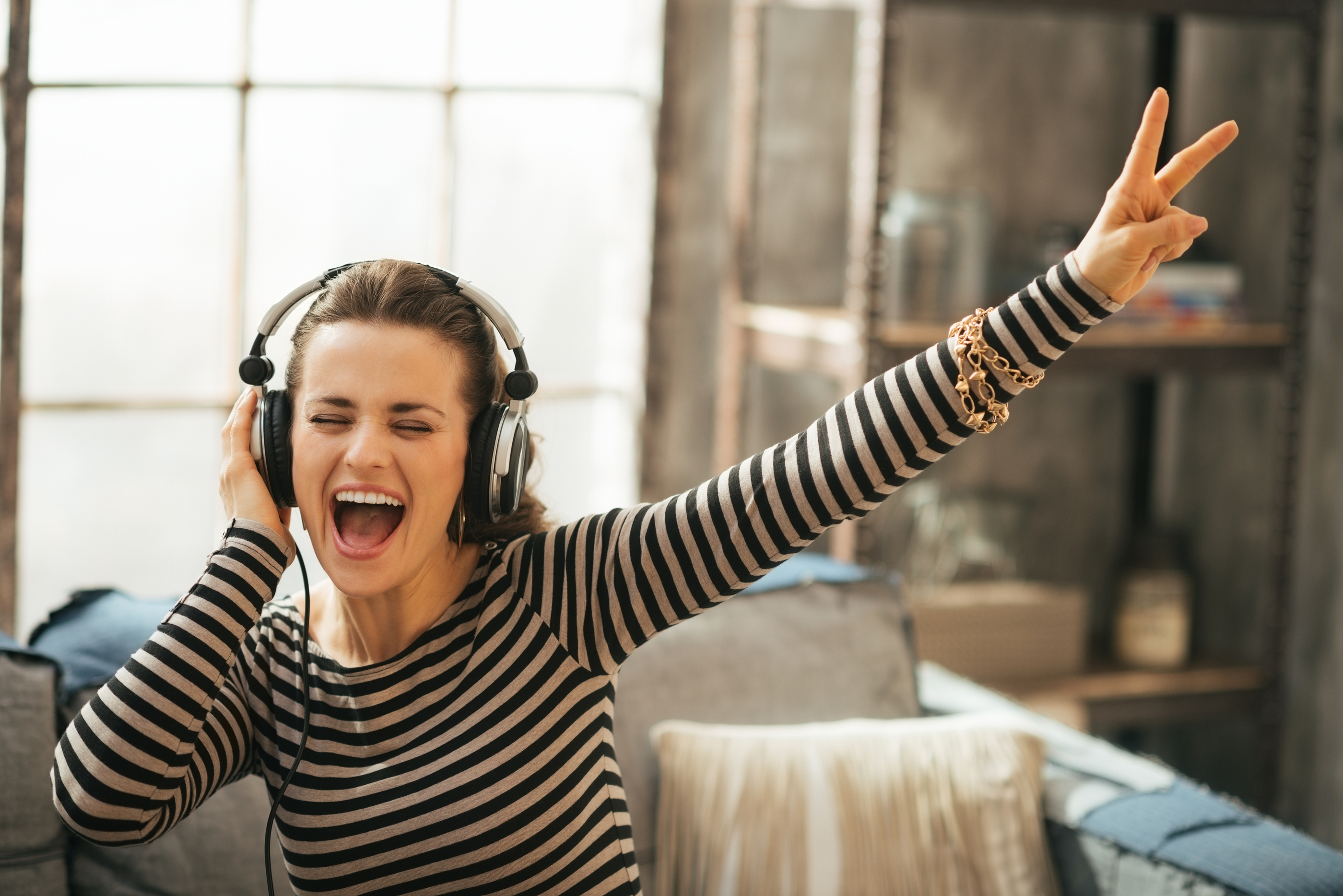 Cheerful Young Woman Listening Music In Headphones In Loft Apart
