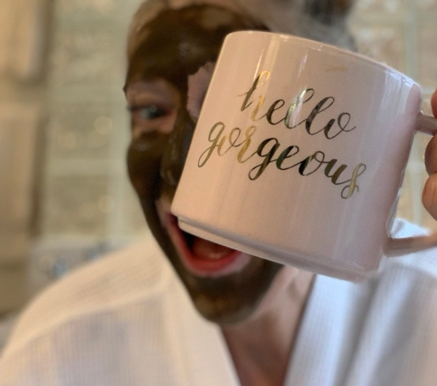 Janice Cox in a coffee facial mask enjoying her morning coffee.