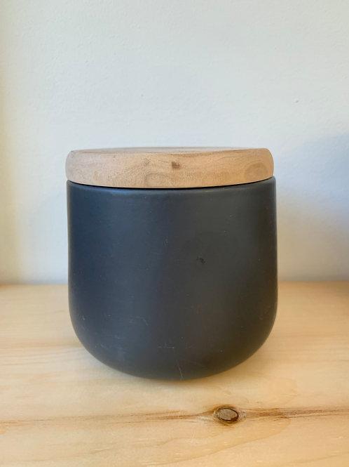 Matte black jar with wooden cap.