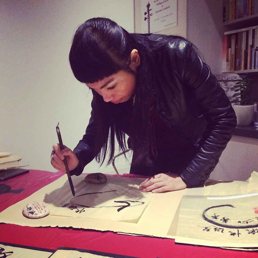 Demonstrating Chinese calligraphy during a fund raising event for a charity