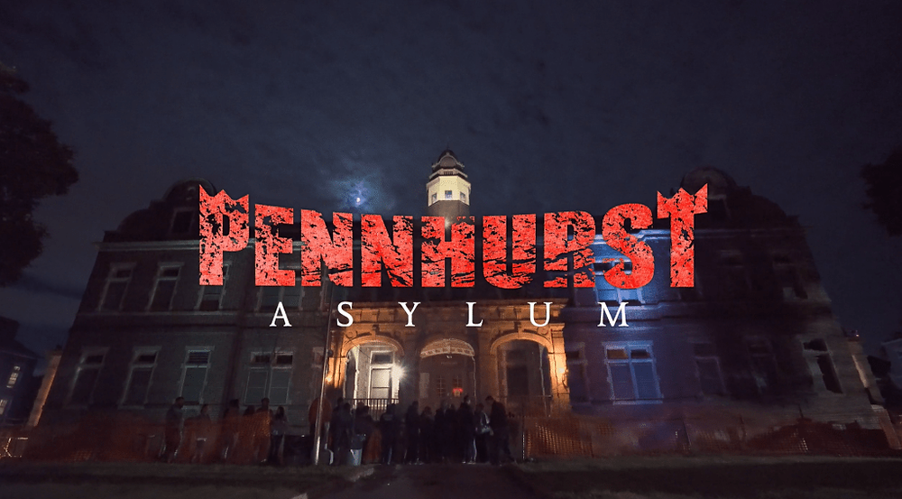 """A photograph of Pennhurst with a line of people waiting to go inside and big red letters that read """"Pennhurst Asylum"""" across the image"""
