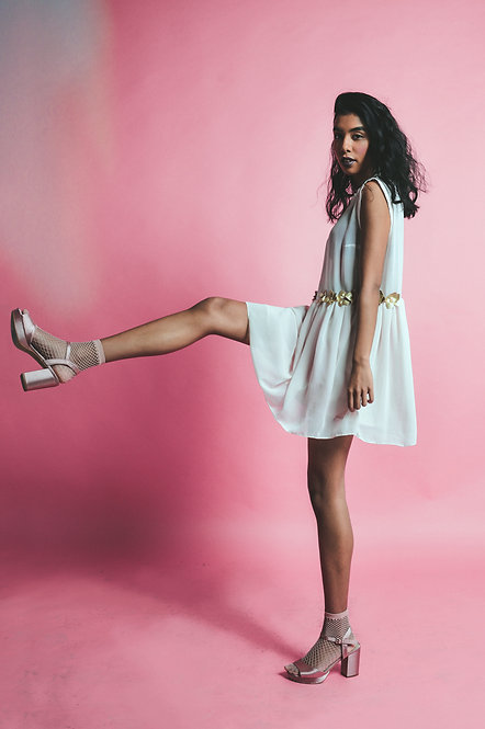 Model posing with the baby pink dress on and matching platform shoes