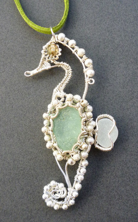 It seemed appropriate to make a seahorse with sea glass! This one is wrapped in silver plated wire with sparkling silver beads.