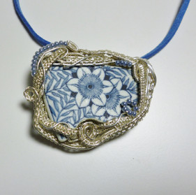 This beautiful piece of pottery was set in silver plated woven wire, with glass seed bead accents.