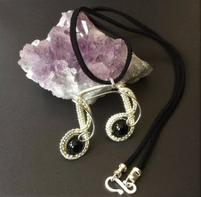 Sterling silver and two black agates formed into a semi-quaver pendant.