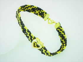 Black and gold woven bracelet with a gold heart embelishment