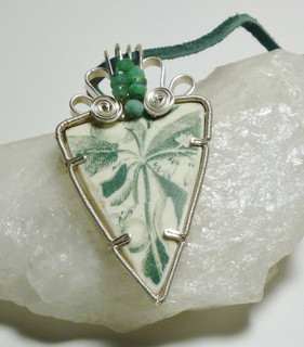 Quite a large, thick piece of pottery which was probably part of a vase or platter. It is set in silver coloured copper tape and silver plated wire, with accents of rough emeralds.