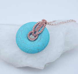 Turquoise donut with an elaborate copper bale