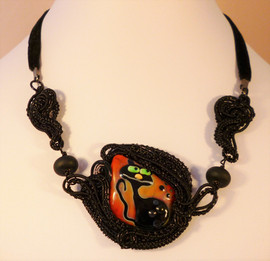 A unique lampwork glass cat bead with woven black wire. Hung on black velvet.