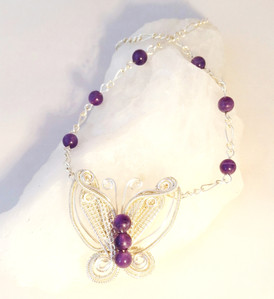 A cute woven butterfly with amethysts in silver plated wire weaving.