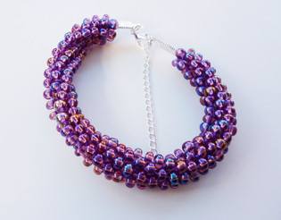Purple rainbow beaded bracelet using Kimihimo braiding techniques