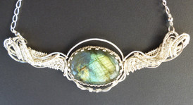 Labradorite oval mounted in sterling silver on a wire woven necklace.