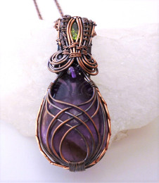 Large amethyst cabochon wrapped in antiqued copper wire, with a faceted peridot hiding in the bale.