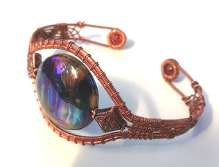 A stunning, unique glass focal bead in bright copper with amber and copper beads.