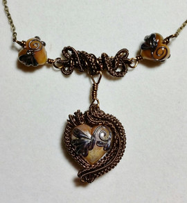 Handmade lampwork beads with woven antique bronze wire.
