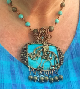An ornate elephant in antique bronze wire and beads is mounted on a turquoise coloured palm stone. It hangs from a necklace of turquoise and antique bronze beads.