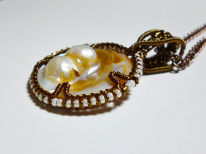 A very unusual, vintage, pearl disc wrapped in antique bronze with ivory coloured seed beads.