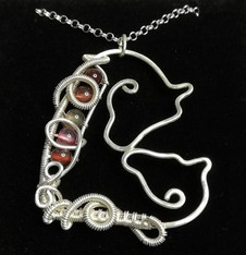 A mare and foal in sterling silver with tourmaline accents.