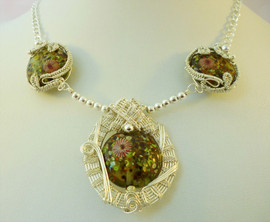 Unique, handmade lampwork glass beads in woven silver plated wire.