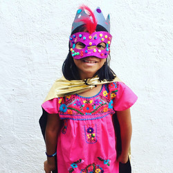 Photo shows a child smiling at the camera. She is wearing a superhero mask, cape and crown.