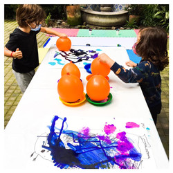 Photo shows two students painting at a table. They are using balloons to print paint on to paper.