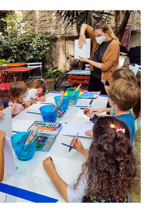 Photo shows a group of children standing at a table. Some are looking at their teacher. The teacher is demonstrating which side of the canvas to work on. The children are checking their own cavases.