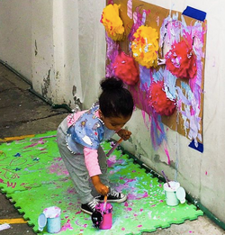 Photo shows a toddler painting on the wall.