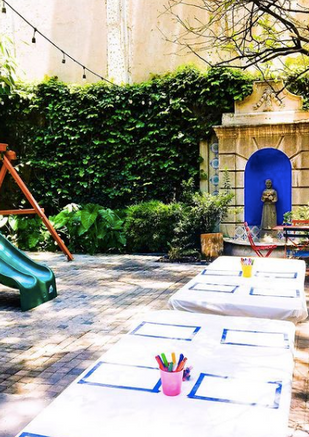 Photo shows the location of the class. There is a slide and swing-set to the left, 2 tables set up with art supplies and a stone sculpture in from of a blue wall at the back.